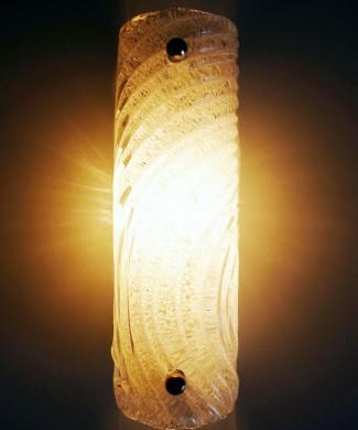 Estructura de acero lacado, con dos brazos de latón dorado que soportan la cubierta de grueso cristal traslúcido.