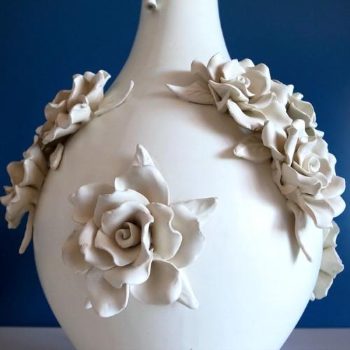 Original y elegante diseño en forma de jarrón con aplicaciones de racimos de flores y hojas
