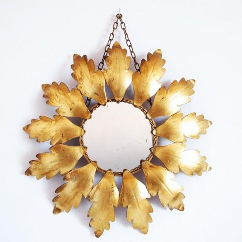 Espejo sol en forja dorada, con diseño de hojas y cadena para colgar. Vintage años 60.