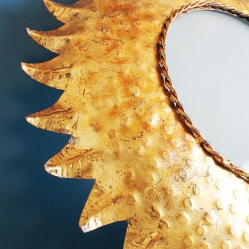 Lámpara de techo o suspensión, con diseño en forma de sol de rayos u hojas doradas.