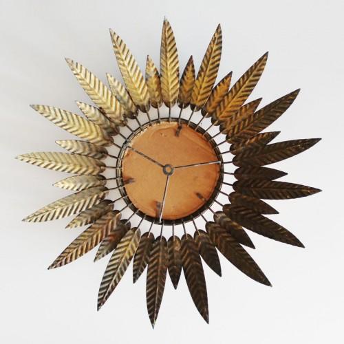 Espejo sol en forja dorada, con diseño de hojas o plumas. Vintage años 60.